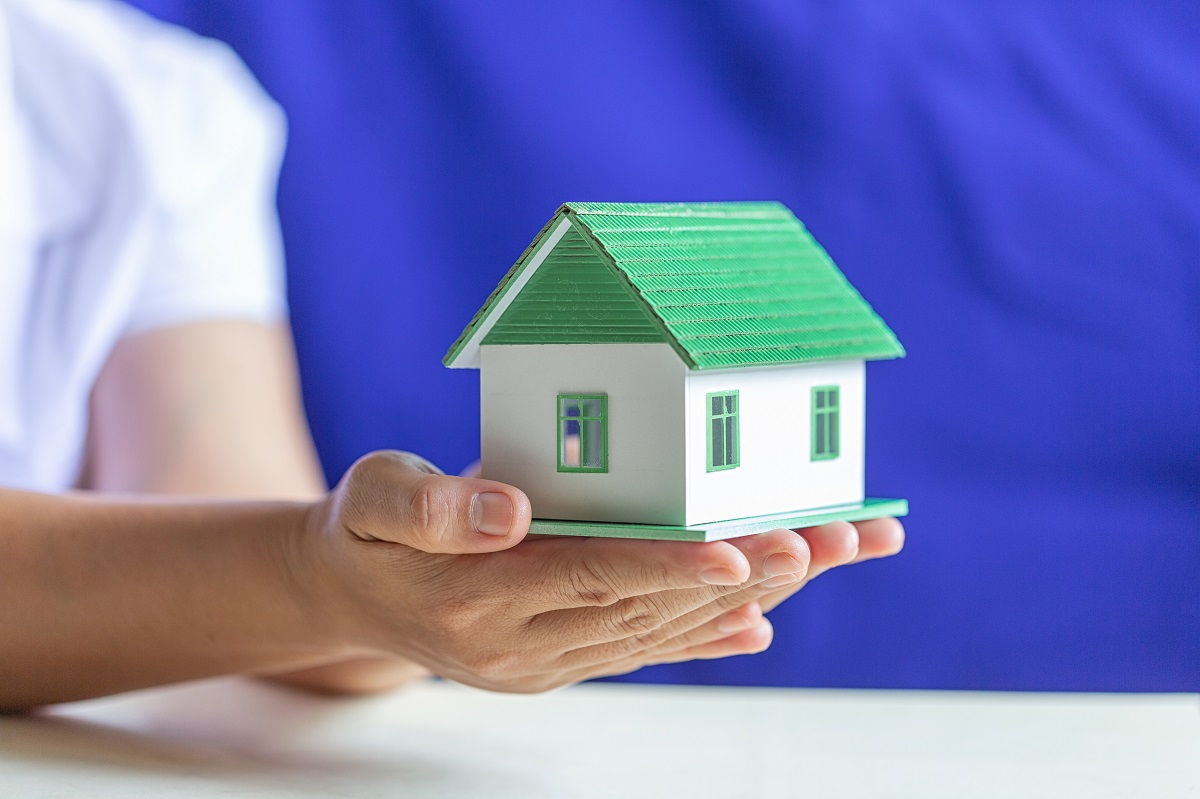 Human Hands Holding Model Of Dream House, Loans And Investments